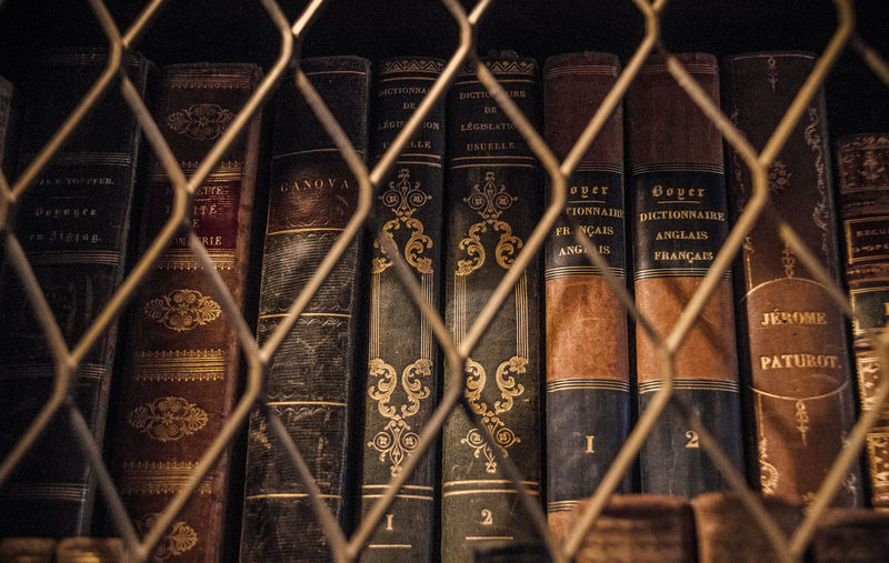 Low Angle View Of Old Books Arranged In Shelf Seen Through Metal Fence In Library