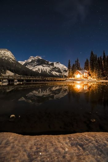 Scenic view of lake by snowcapped mountains against sky at night