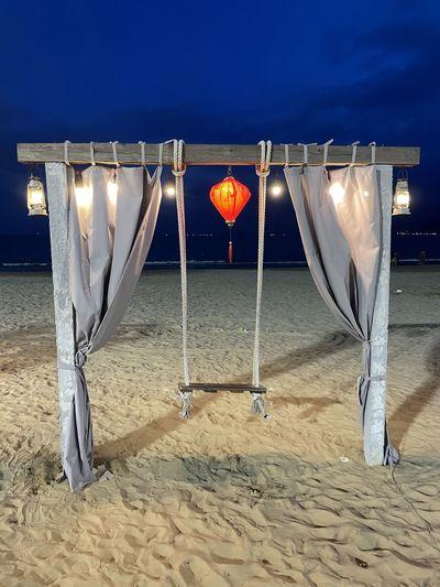 Illuminated lighting equipment hanging on beach against sky at night