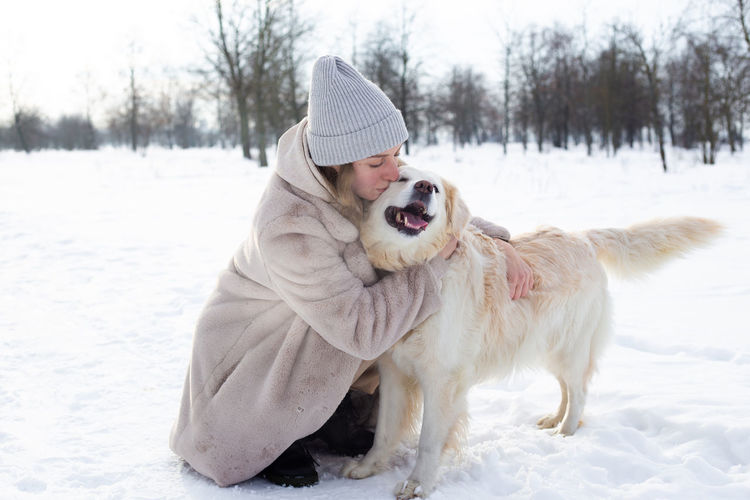 Woman with dog on snow covered land