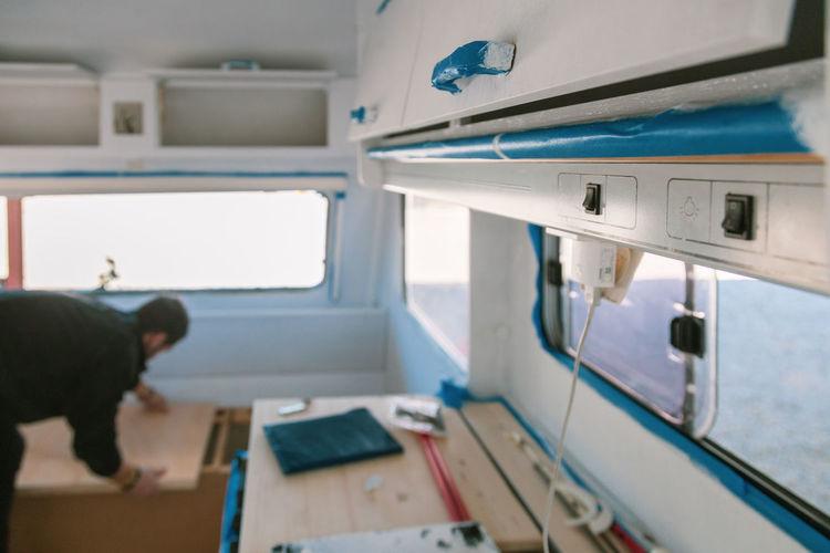 Man adjusting wood in camper trailer