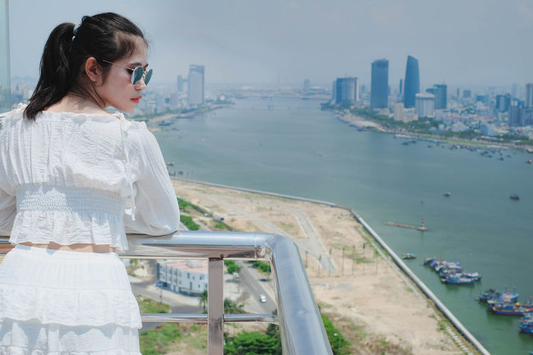Woman looking at cityscape by sea against sky