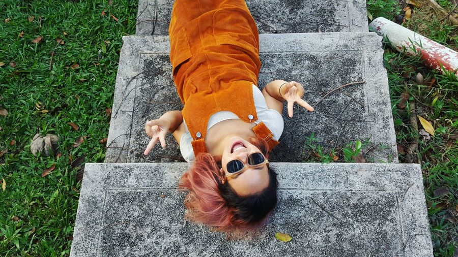 High Angle Portrait Of Young Woman Lying On Steps