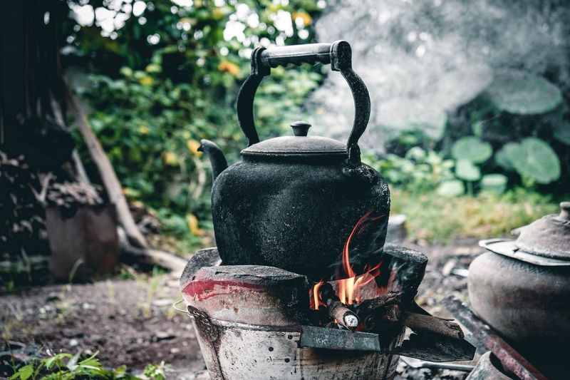 Close-up of kettle on camping stove in forest