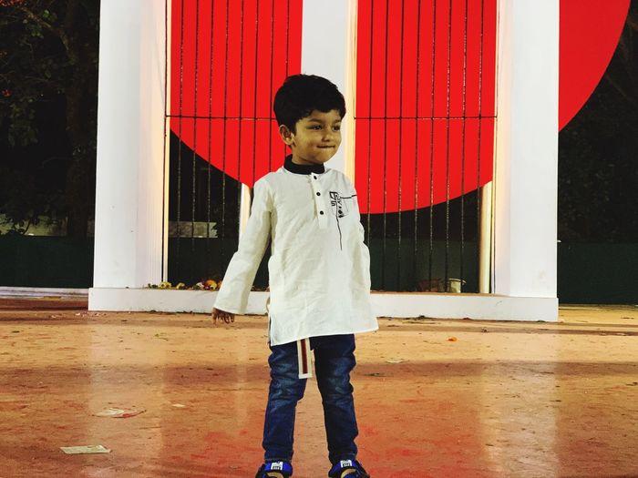 Cute boy looking away standing on floor
