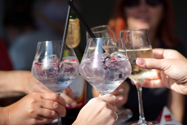 Closeup of cocktail in elegant glasses - group of people toasting