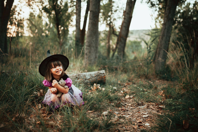 Girl holding toy while sitting on land in forest