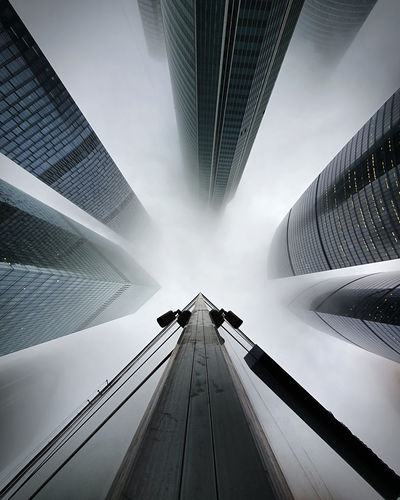Low angle view of modern buildings during foggy weather