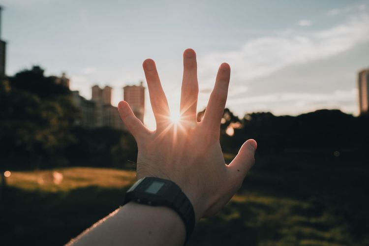 Hand of person against sunset sky