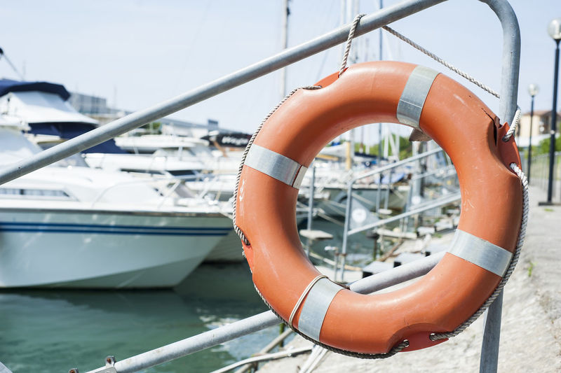 Orange life buoy hanging from a railing at the port. Close-up Day Floating On Water Life Belt Life Buoy Life Vest Mode Of Transport Nature Nautical Vessel One Person Outdoors Real People River Sky Transportation Water