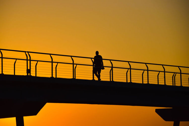 Walk over the bridge Architecture Beauty In Nature Bridge Bridge - Man Made Structure Built Structure Clear Sky Connection Copy Space Leisure Activity Lifestyles Men Nature One Person Orange Color Outdoors Railing Real People Sea Silhouette Sky Standing Sunrise Sunset