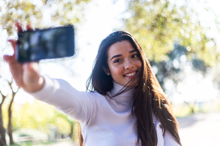 Close-up of smiling young woman taking selfie outdoors
