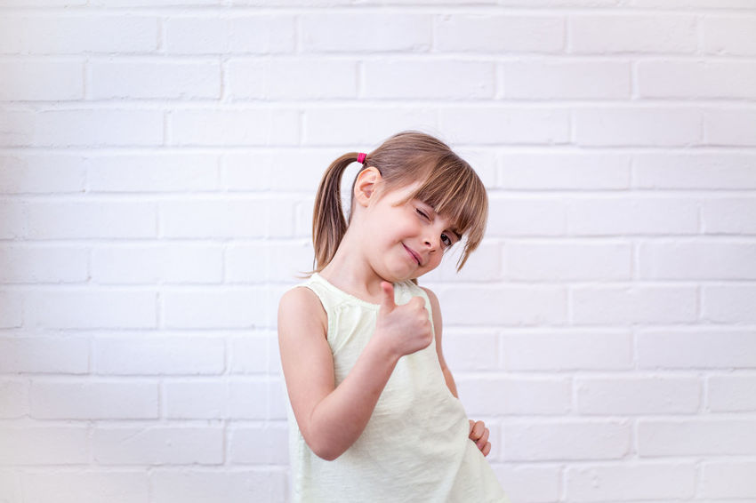Attractive little blonde girl child giving thumbs up and winking at viewer. Cute kid against white brick wall Adult Blond Hair Brick Wall Child Child Portrait Childhood Children Only Cool Day Elementary Age Eyeem People EyeEm Portraits Girls Happiness Happy Indoors  One Girl Only One Person People Portrait Standing Waist Up White Background White Color