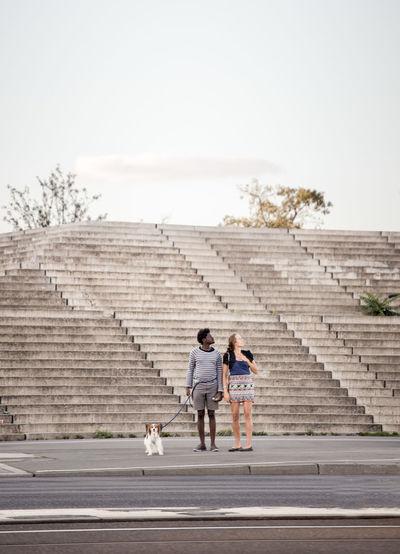 Children walking on steps against sky