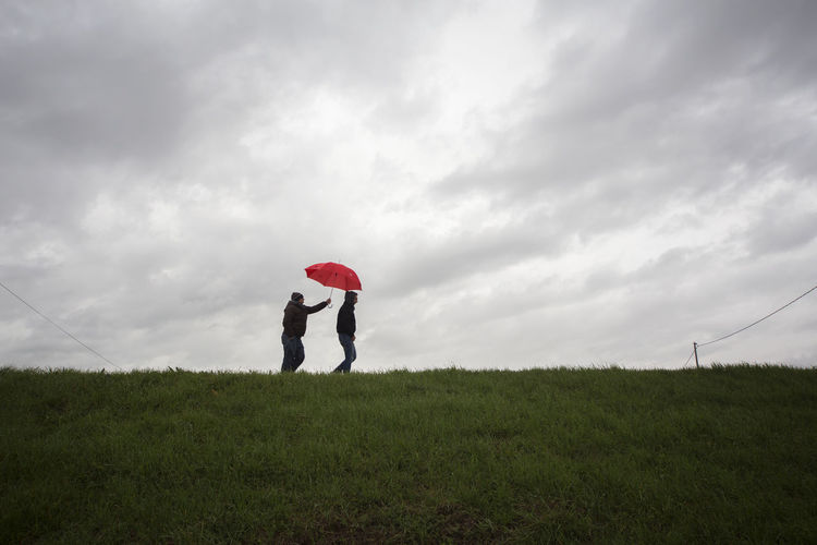 Side view of men sharing red umbrella on hill against cloudy sky