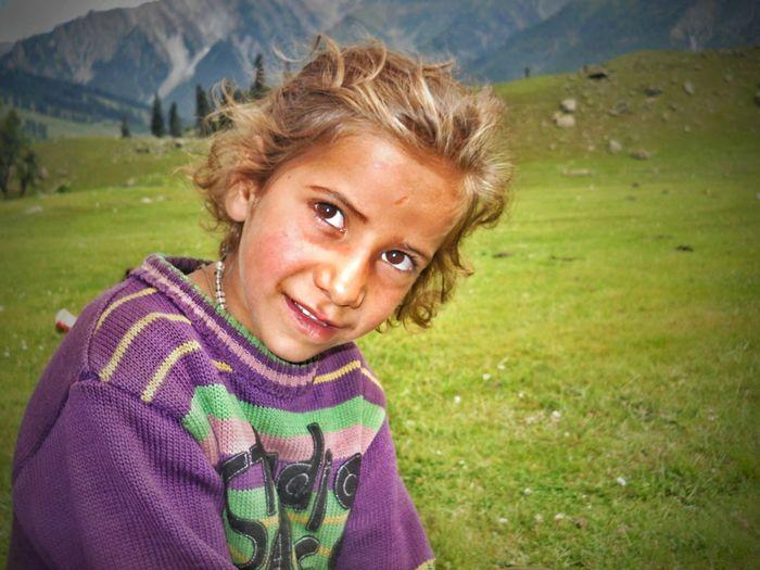 Smiling Girl Wearing Sweater Looking Away On Field