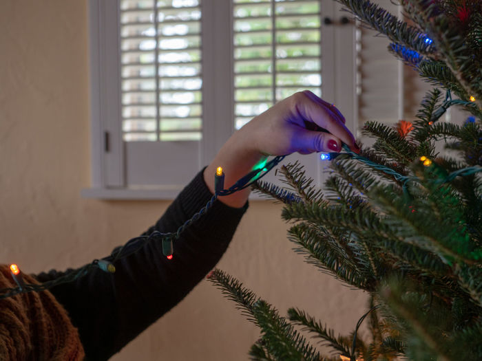 Cropped hand decorating christmas tree
