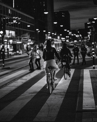 Rear view of people riding bicycle on road at night