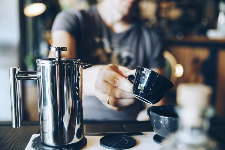 Midsection of man having coffee in cafe