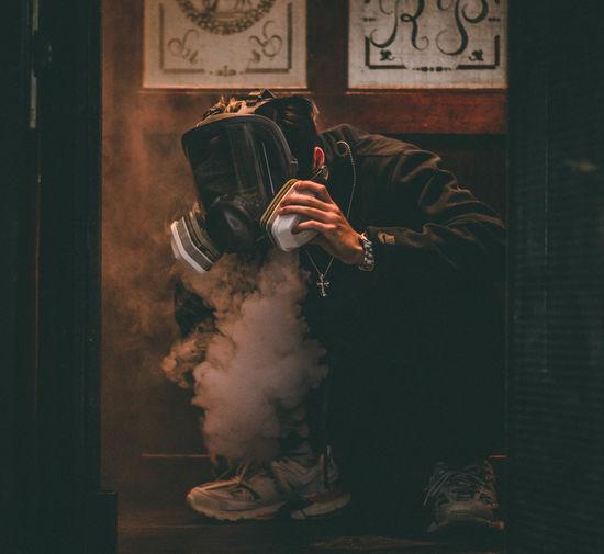 Man wearing gas mask crouching over smoke