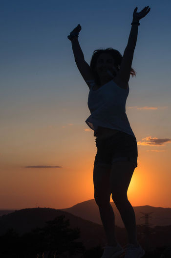 Woman with arms raised standing on beach against sky during sunset