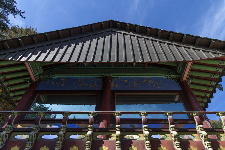 Low angle view of roof of building against blue sky