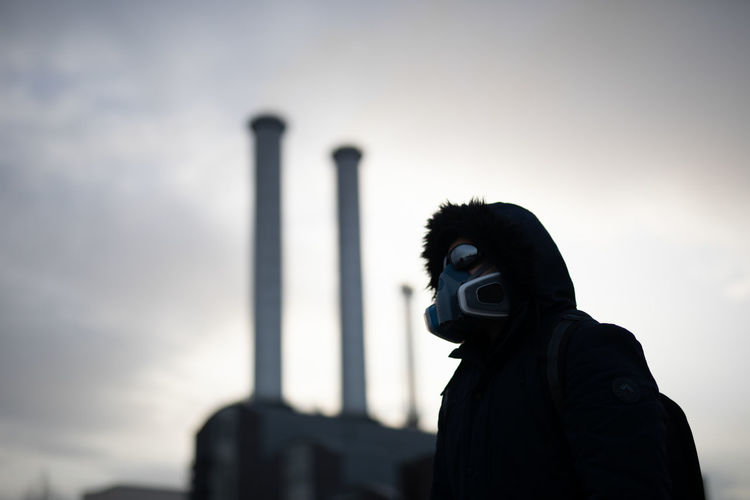 Low angle view of person with mask standing against sky after worldwide  epidemic of coronavirus in