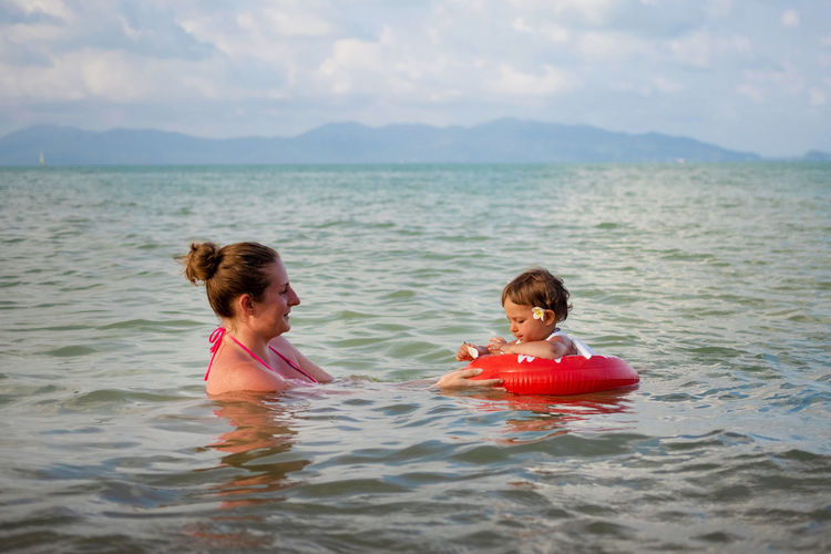 Full length portrait of mother and daughter in water