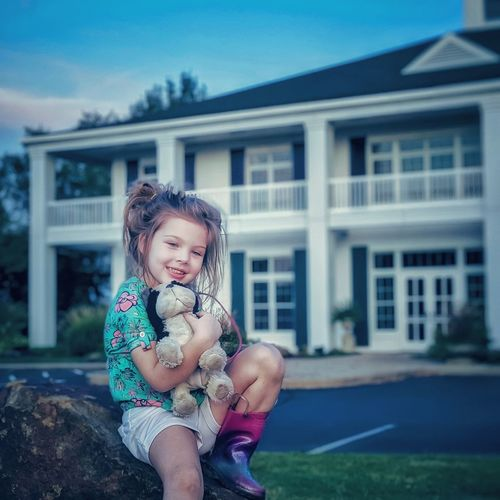 Portrait of girl sitting with stuffed toy on rock