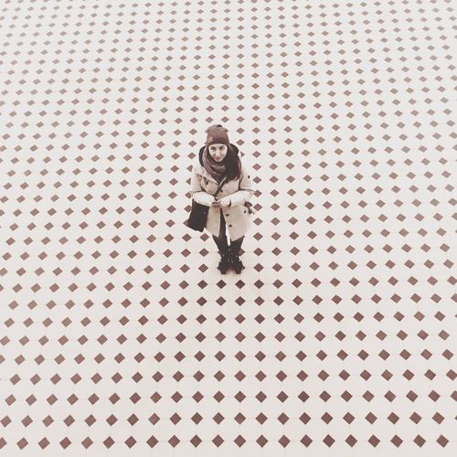 High angle portrait of woman standing on tiled floor