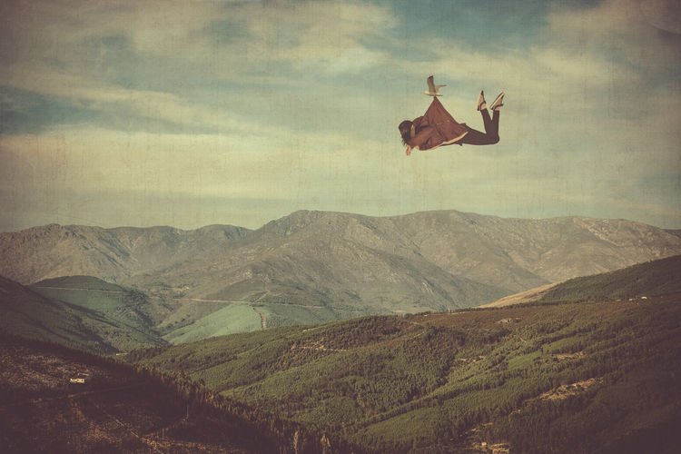 Digital Composite Image Of Bird Lifting Woman While Flying Over Landscape
