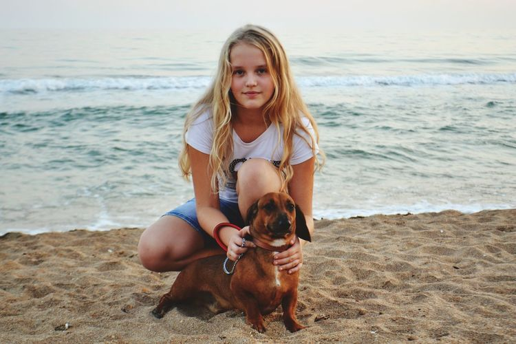 Portrait of girl crouching with dog at beach