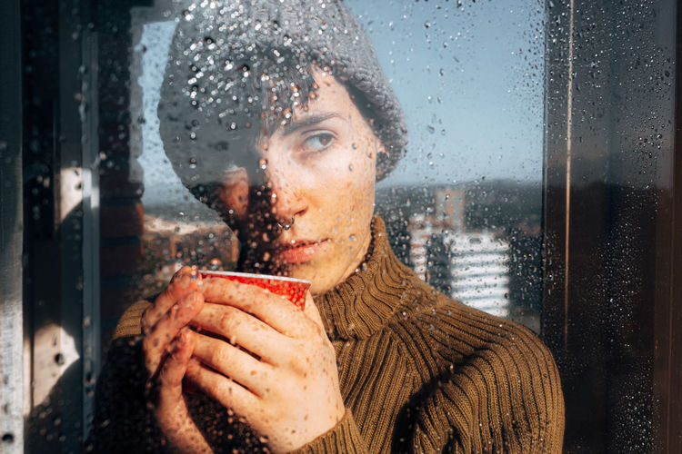 Portrait of woman looking through wet window