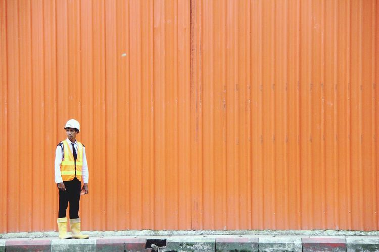 Manual worker wearing reflective clothing and hardhat standing against orange corrugated iron