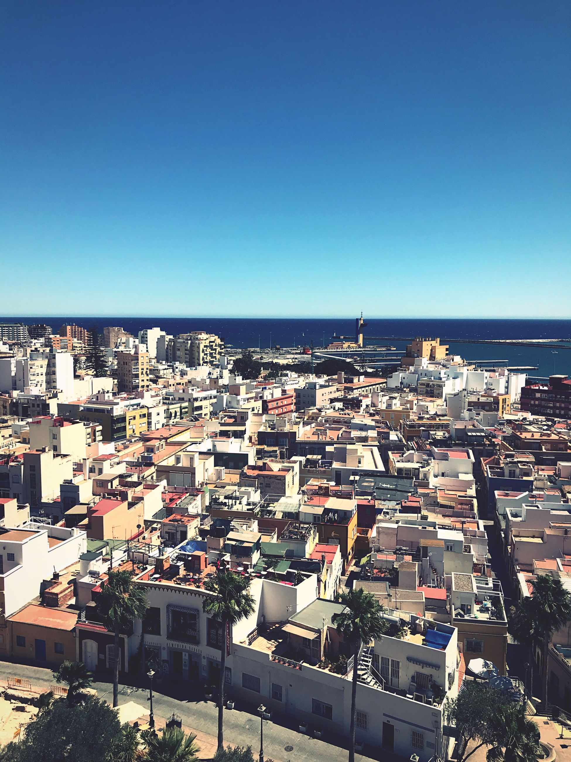 building exterior, architecture, sky, built structure, city, building, clear sky, residential district, cityscape, copy space, blue, crowd, crowded, nature, high angle view, day, sea, sunlight, horizon, outdoors, horizon over water, townscape, settlement