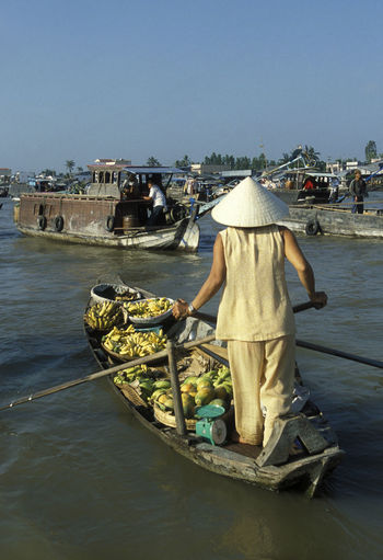 Rear view of male vendor on floating market against clear blue sky