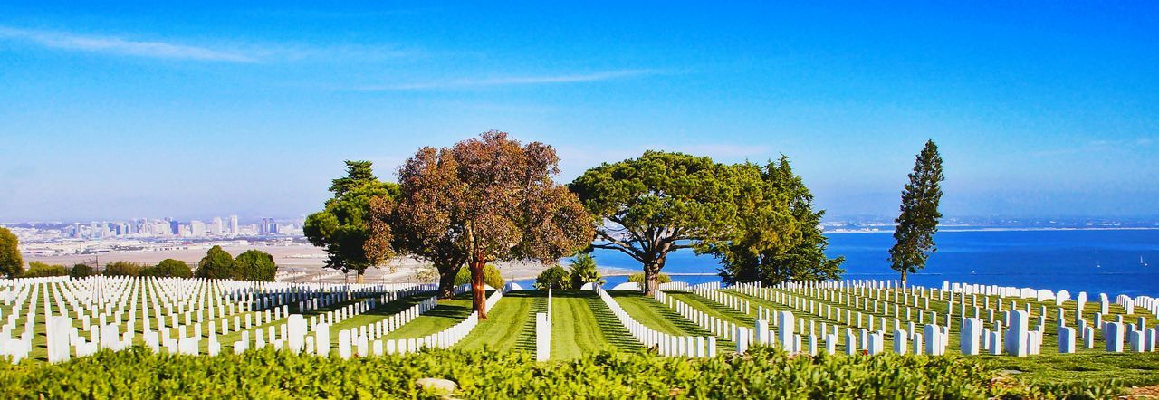 Panoramic View Of Tombstones By Sea Against Blue Sky At Cemetery