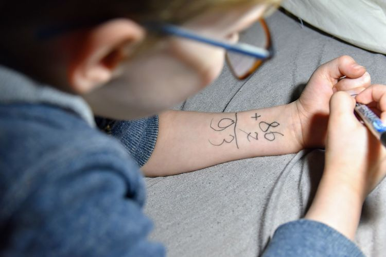 Close-Up Of Boy Writing On Hand