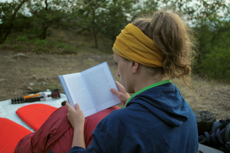 young caucasian female reading book while outdoor camping Backpacking Camping Hiking Nature Reading Travel Trekking Woman Activity Adult Book Casual Clothing Caucasian Concentration Day Education Female Girl Hikingadventures Hobby Holding Land Leisure Activity Lifestyles Nature Note Pad One Person Outdoors Paper People person Publication Reading Real People Relaxation Sitting Tent Vacation Women Young Adult