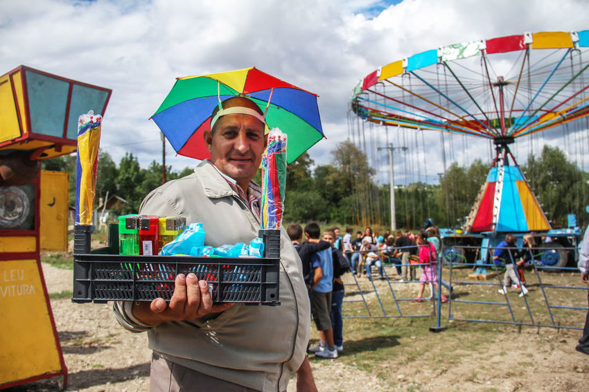 Adult Adults Only Arts Culture And Entertainment Carusell Cheerful Country Fun Day Enjoyment Fun Holding Leisure Activity Men Multi Colored Occupation One Person Only Men Outdoors People Real People Reportage Seller Sky Smiling Young Adult This Is Masculinity