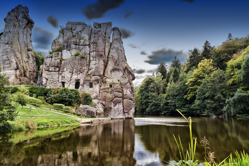 The Externsteine, striking sandstone rock formation in the Teutoburg Forest, Germany, North Rhine Westphalia Ancient Civilization Architecture Beauty In Nature Built Structure Day External Stones Externsteine History Lake Mysterious Nature No People Outdoors Rock - Object Rock Landscape Scenics Sky Tourism Toursm Tranquil Scene Tranquility Travel Destinations Tree Water