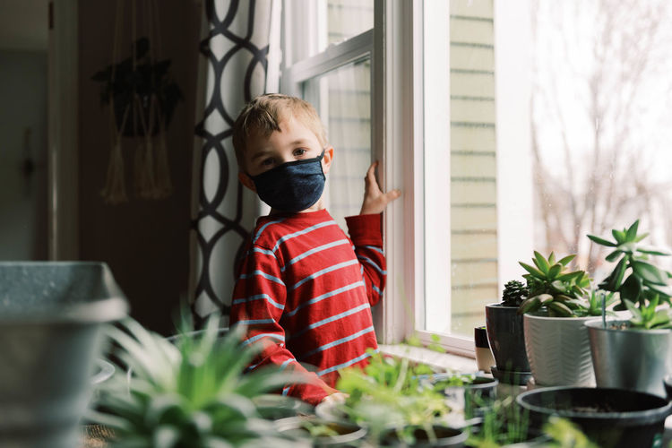 Boy standing by potted plant on table