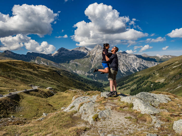Side view of boyfriend carrying girlfriend while standing on mountain against sky