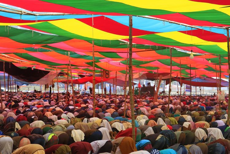 Group of people under colourful roof for prayer