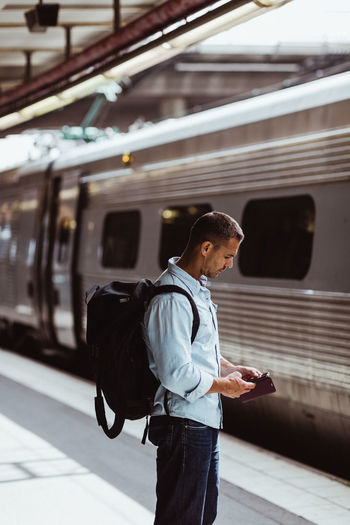 Side view of man using mobile phone at railroad station