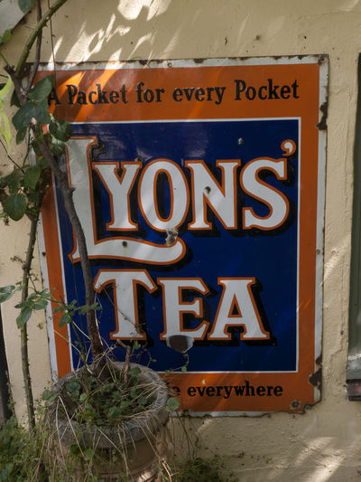 Man Cave Signs in back garden Shoreham Kent Advertising Back Shed Black Out Board Day Hovis Kent Looting Lyons Tea Man Cave News Of The World No People Old Tin Signs Outdoors Plane Wreckage Robinsons Signs Text Village Vivid International