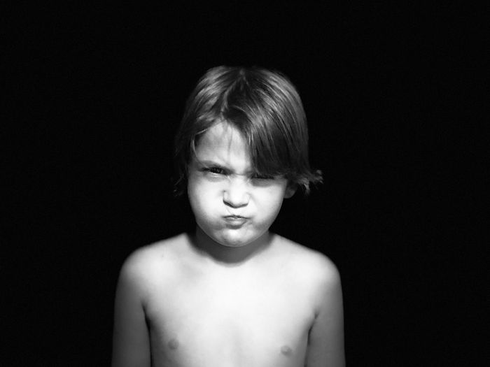 Portrait of shirtless boy sulking against black background