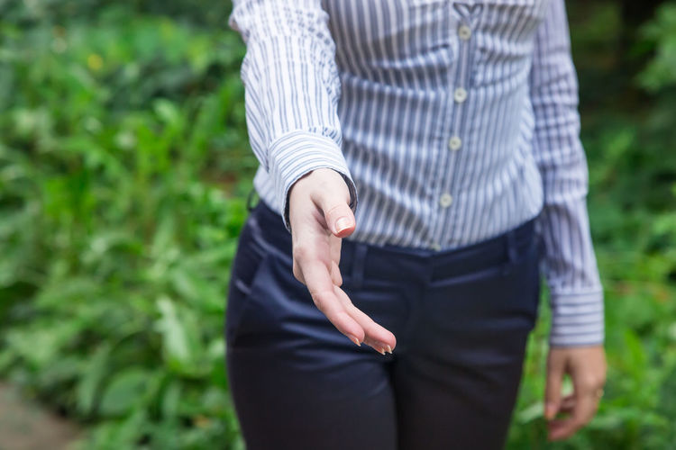 Midsection of businesswoman giving handshake while standing against plants at park