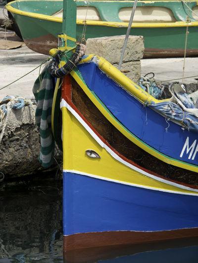 Close-up of fishing boat moored at lake