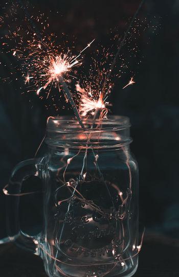 Close-up of illuminated sparklers in mason jar